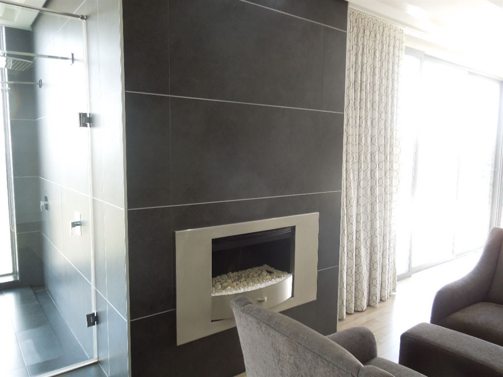 Gas fire place set in timber paneling in Master suite