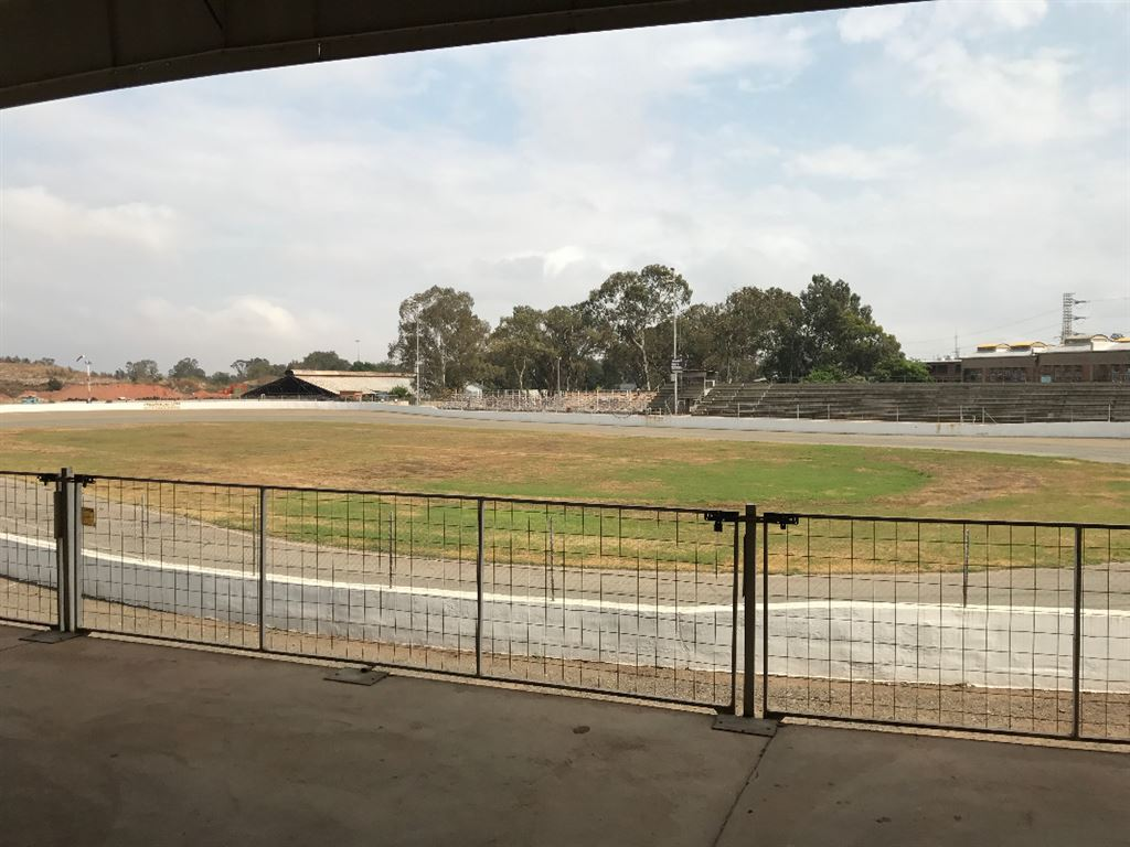 View from Clubhouse over the extensive open area featuring the Race Track and some of the Grandstands.