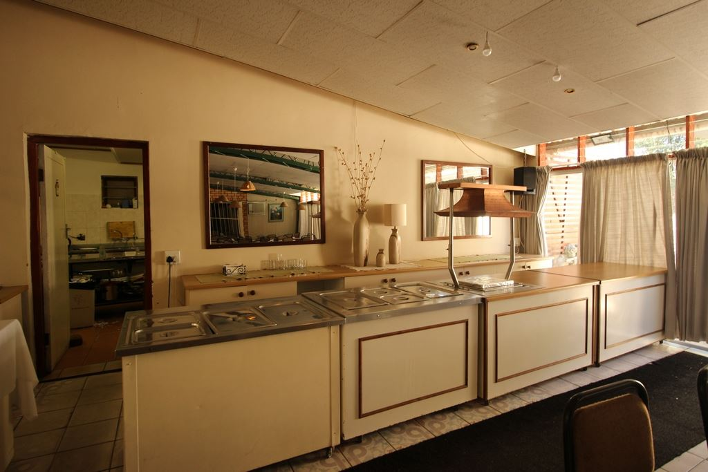 Serving area of the dining hall with doorway to the kitchen in back left