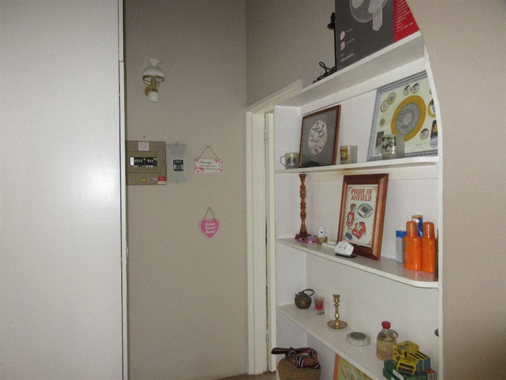 Hall way to bedroom one with built-in book shelf