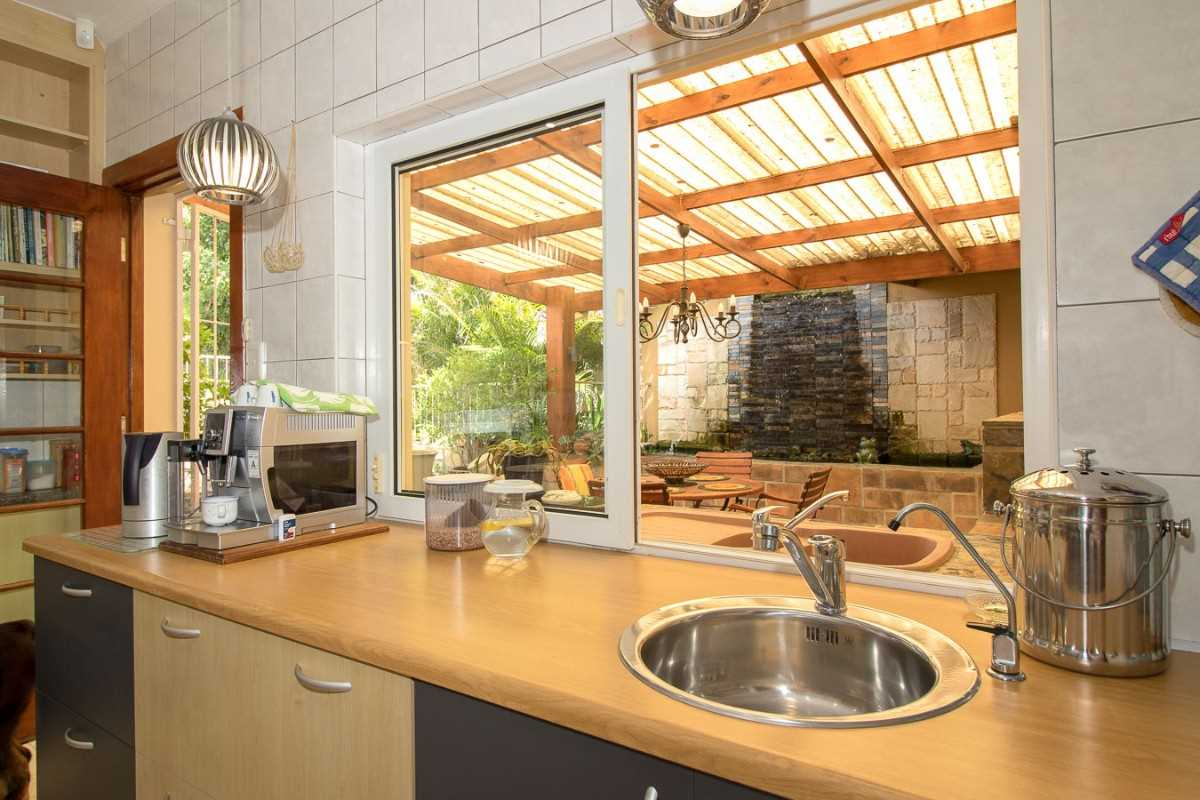 Double Storey Family Home with Flat For Sale In Port Alfred, view from the kitchen of the under cover entertainment area and koi pond.