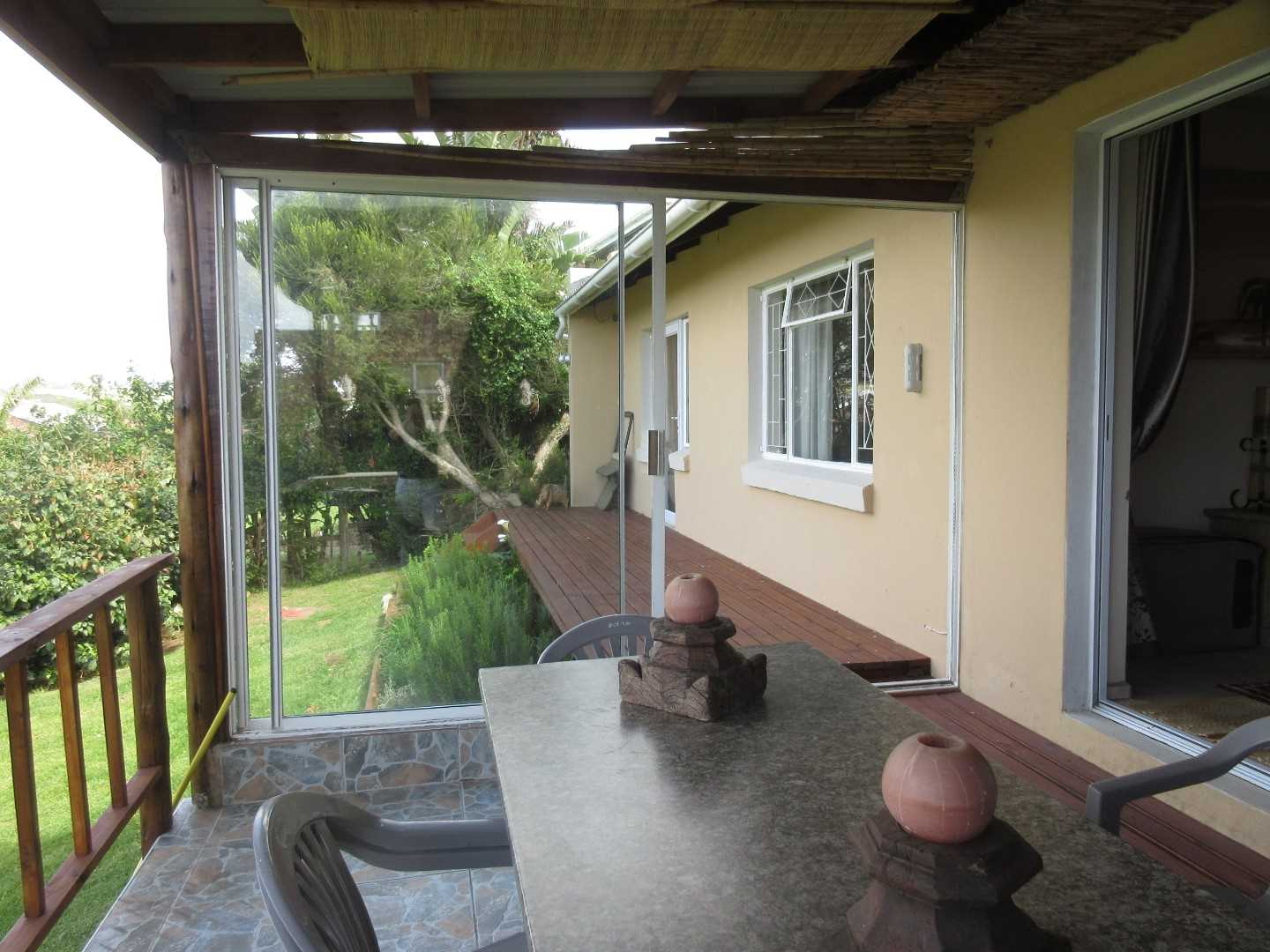 Covered entertainment area with built in braai and sliding doors to block the West wind