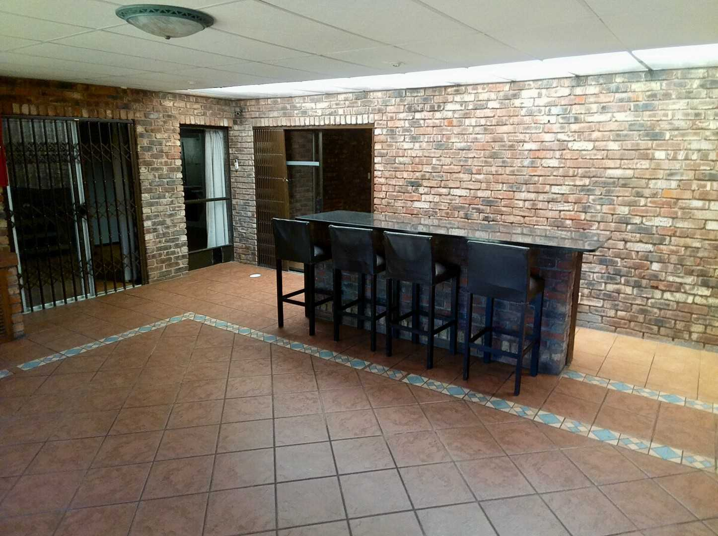 Large living room with build in braai with aircon and sliding doors to back garden