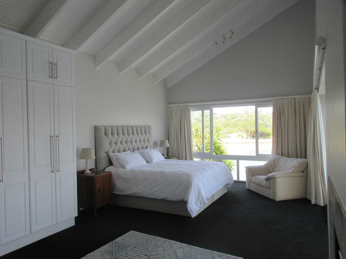 Master bedroom with plenty of built-in cupboards, open fire place, en-suite bathroom and balcony access