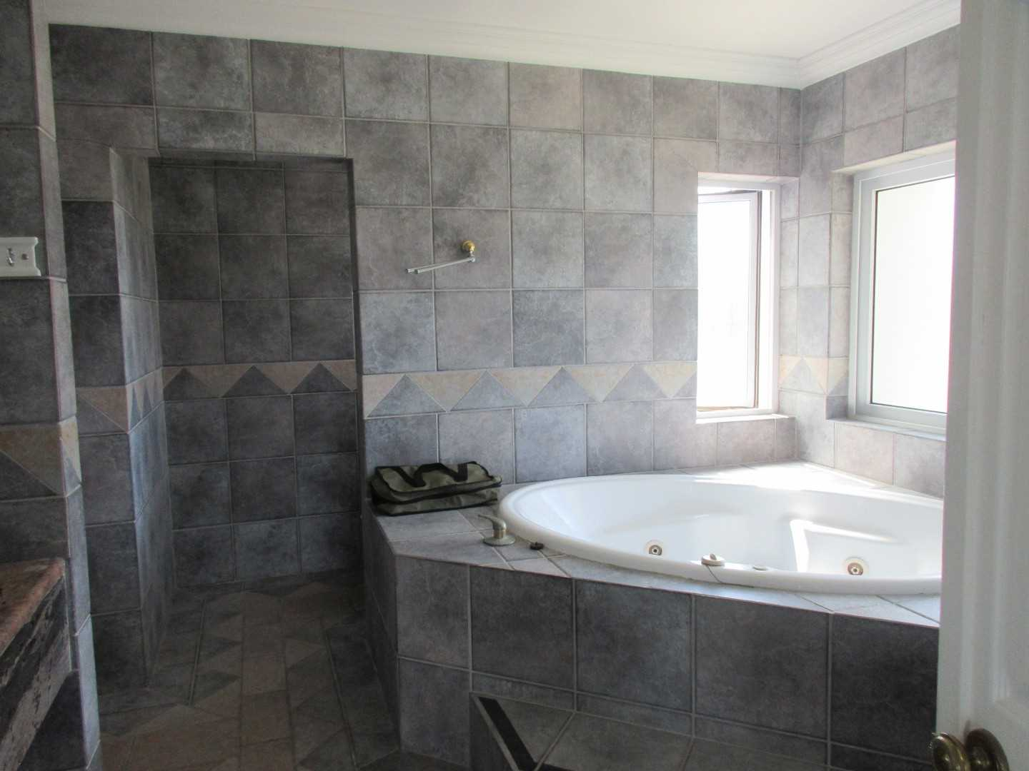 Master en-suite bathroom with spa bath, shower, toilet and basins