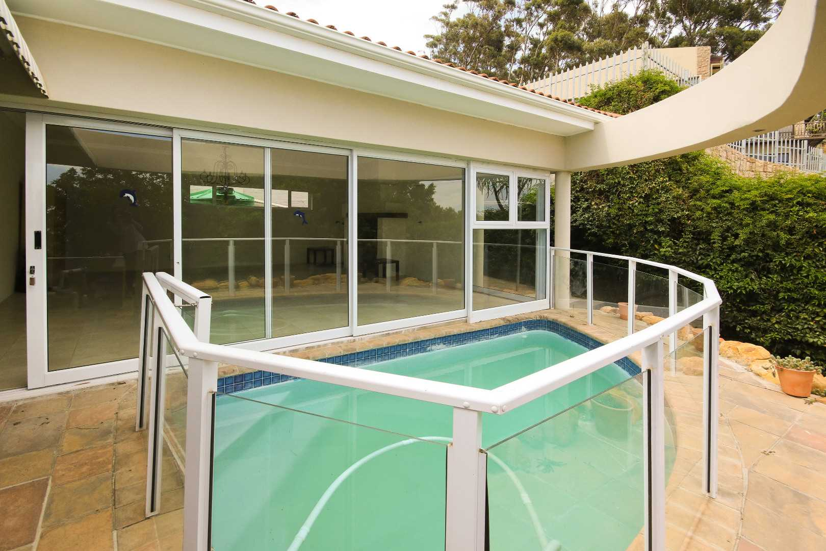 Upper level swimming pool with ease of access to braai lounge and built in braai fireplace