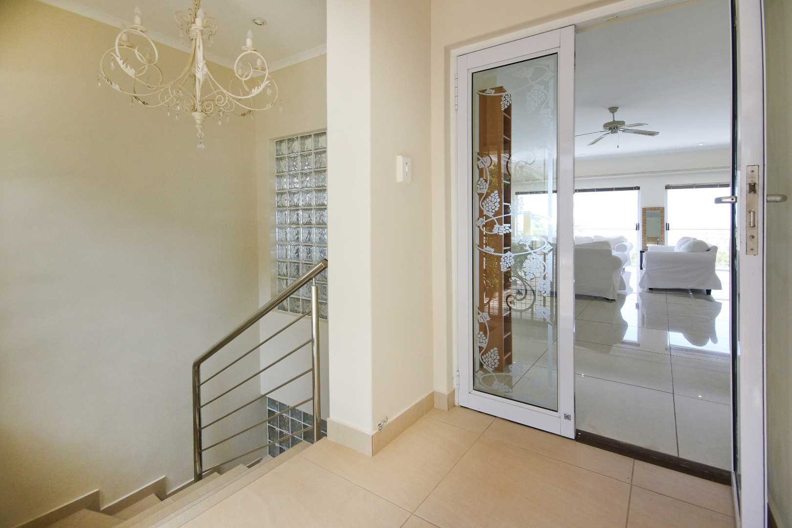 Secure entrance hall beyond sliding front door with security gate.