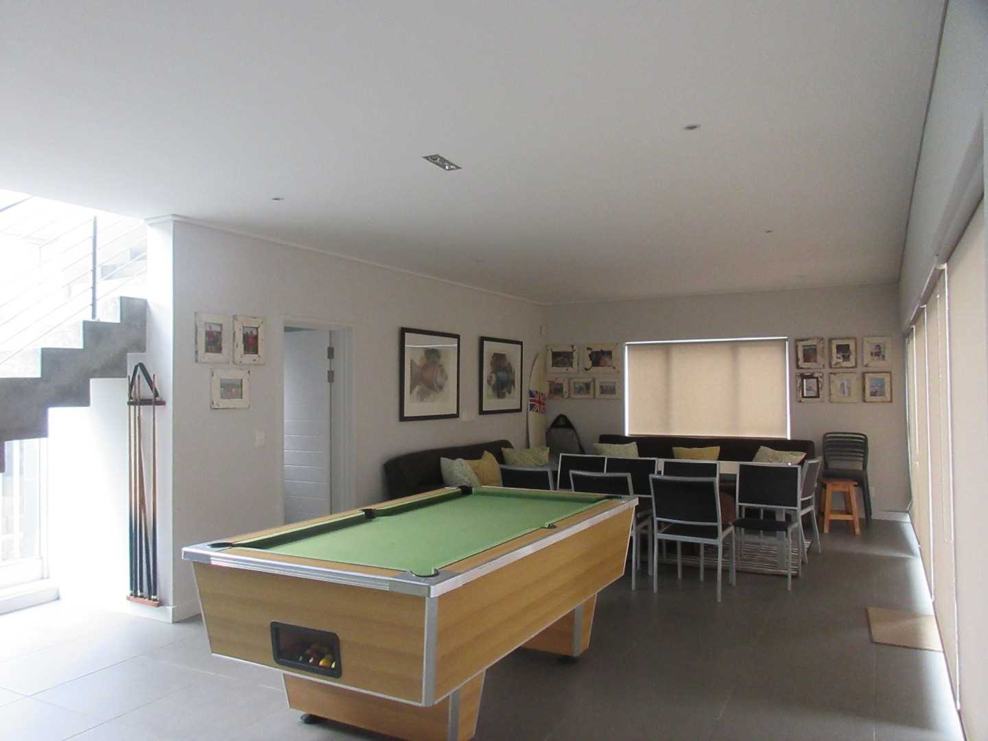entertainment area and snooker room with guest bathroom and stacker doors leading to the pool area