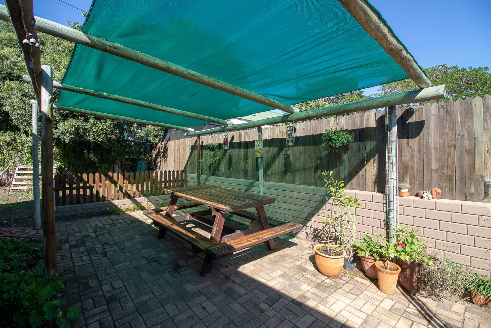 Shade-clothed carport and vegetable garden