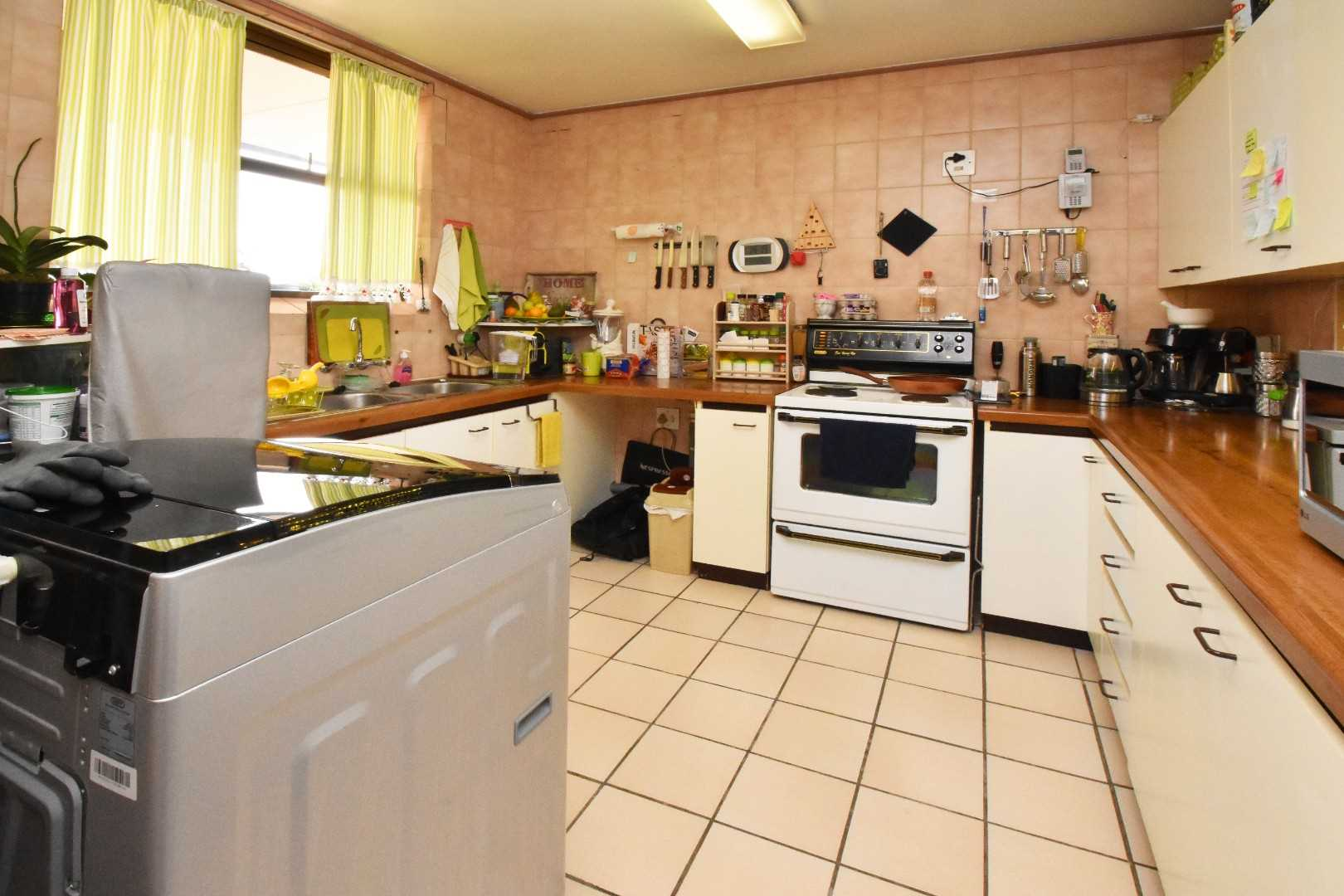 Kitchen overlooks lounge, space for fridge, washing machine and all your extras