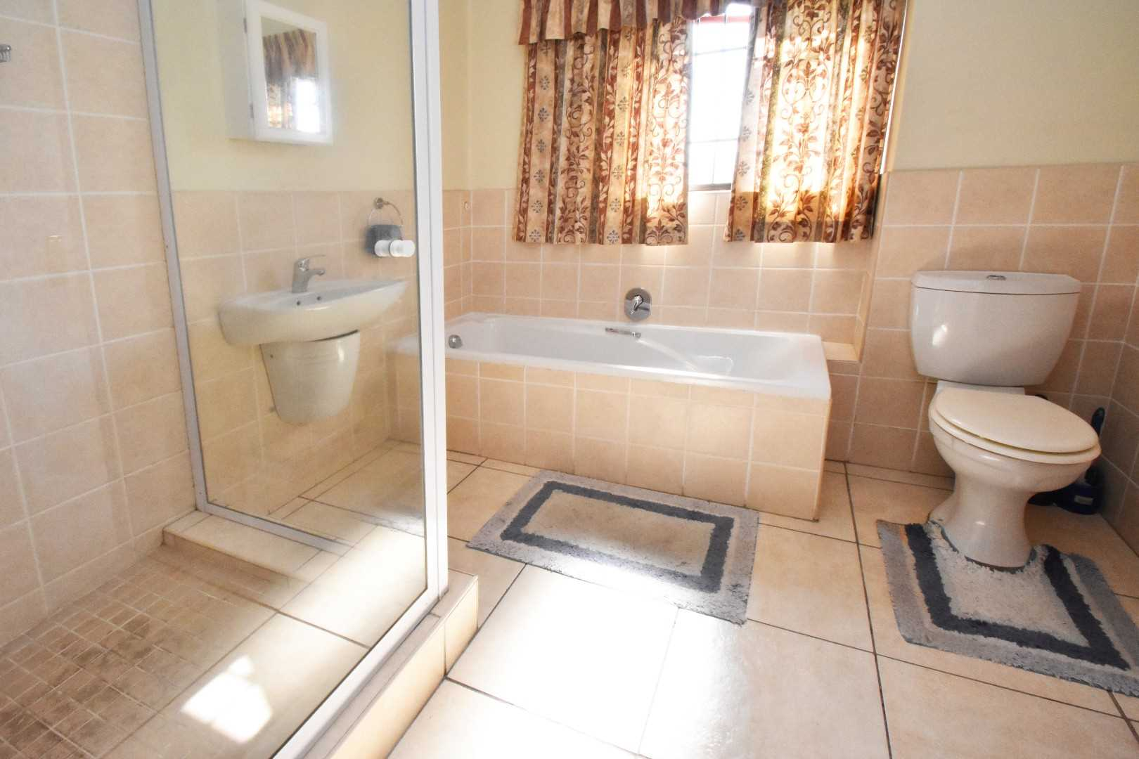 Full guest bathroom with bath and shower