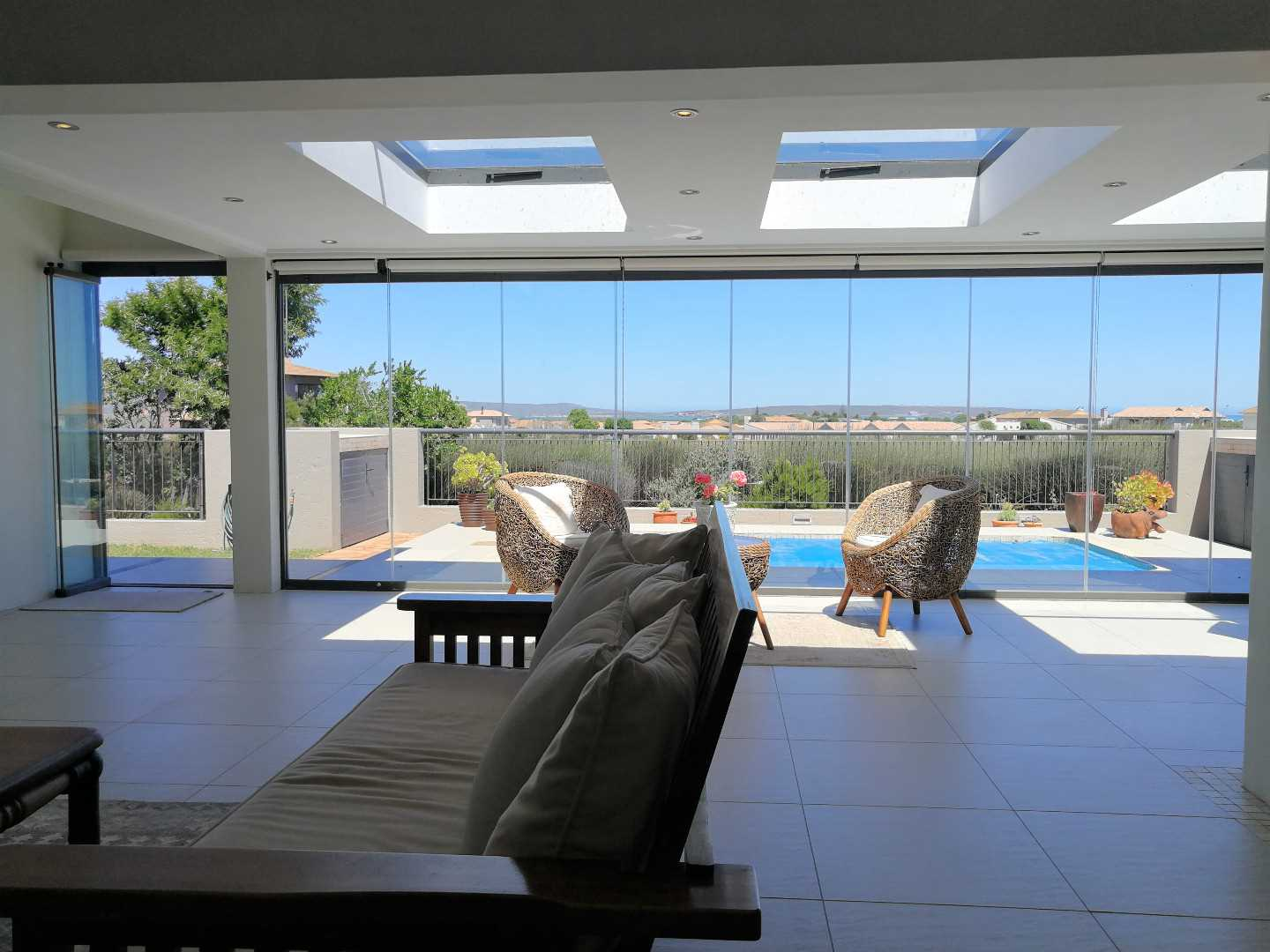 Spacious Sun room / 2nd lounge with a custom built pub and overlooking the pool and views