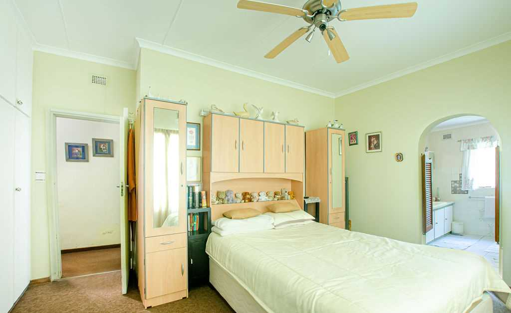 Master bedroom with en-suite full bathroom and ceiling fan as well as air conditioner
