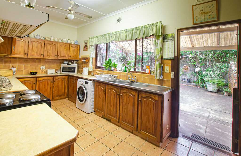 Spacious kitchen with kitchen door opening onto covered verandah which leads into gorgeous garden